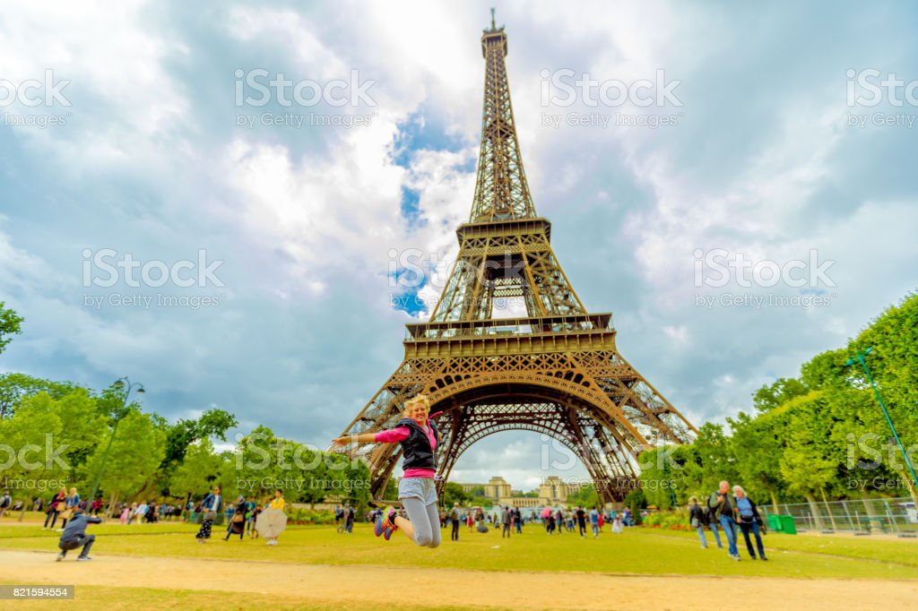 Woman jumping at Tour Eiffel stock photo