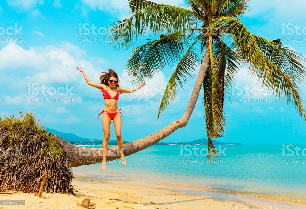 Woman jumping at tropical beach stock photo