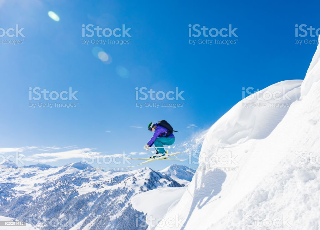 Woman jumping during skiing day in the Pyrenees Baqueira Beret Catalonia Spain stock photo