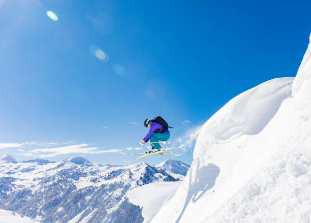 Woman jumping during skiing day in the Pyrenees Baqueira Beret Catalonia Spain Woman jumping during skiing day in the Pyrenees Baqueira Beret Catalonia Spain land feature stock pictures, royalty-free photos & images