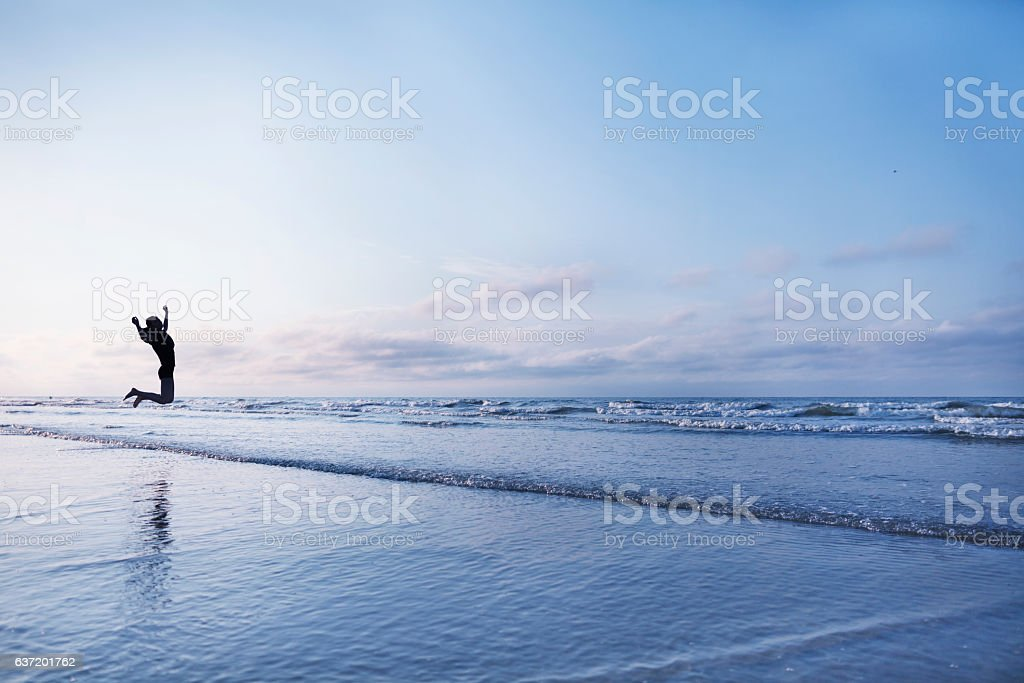Woman jumping for joy on beach at sunrise - foto de acervo