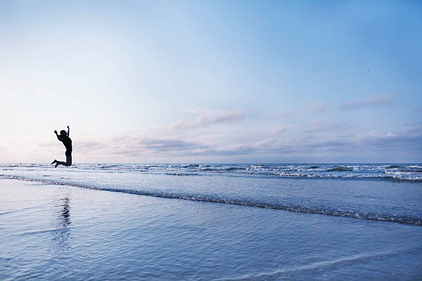 Woman jumping for joy on beach at sunrise – Foto
