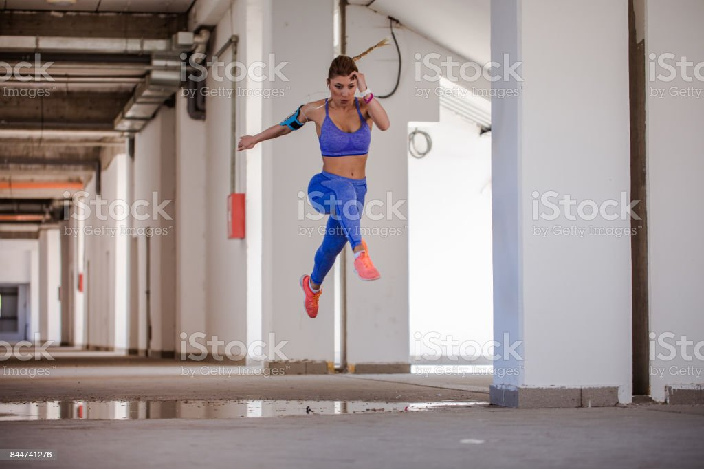 Woman jumping in hallway stock photo