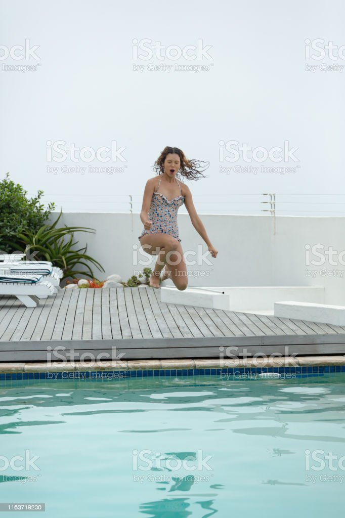 Front view of beautiful Caucasian woman jumping in swimming pool at...