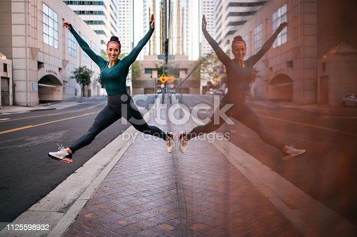 Strong athletic woman jumping in the air next to a marble wall on a street sidewalk in a city center.
