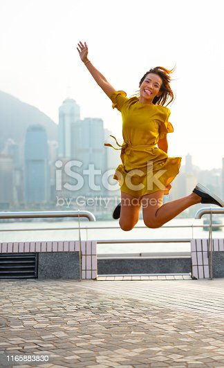 Woman jumping of joy, around at view of famous Victoria Harbour, Hong Kong cityscape