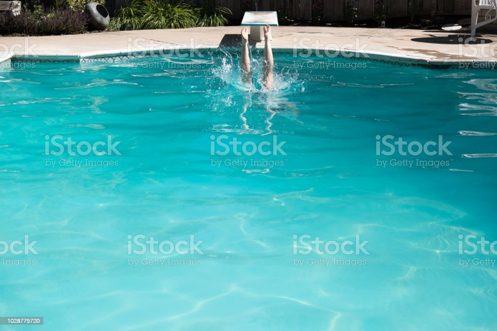 Woman Jumping Off A Diving Board Into A Swimming Pool Legs Above The ...