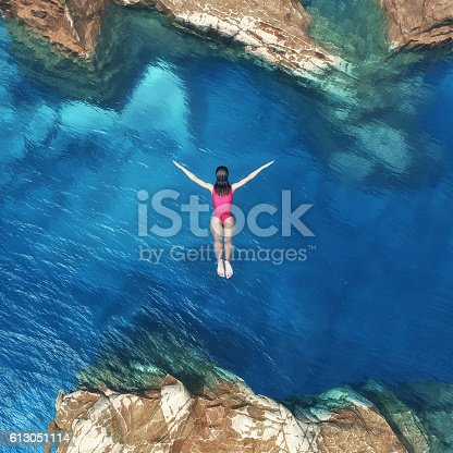 istock Woman jumping off cliff 613051114