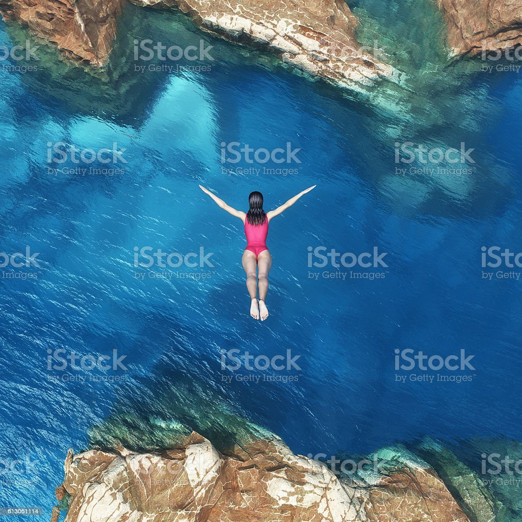 Woman jumping off cliff stock photo