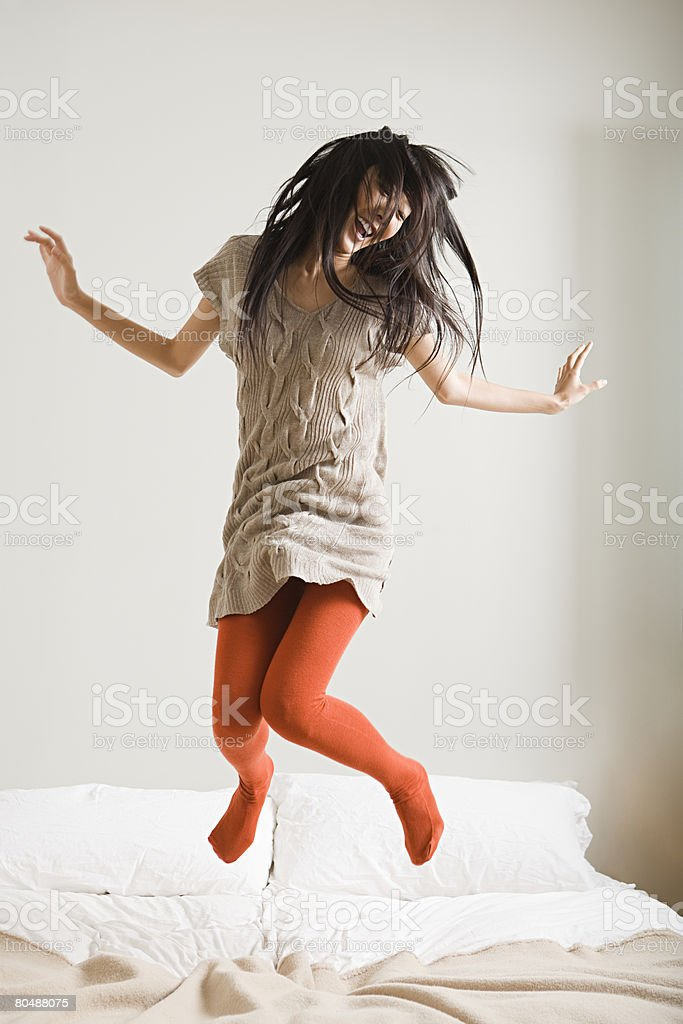 Woman jumping on bed 免版稅 stock photo
