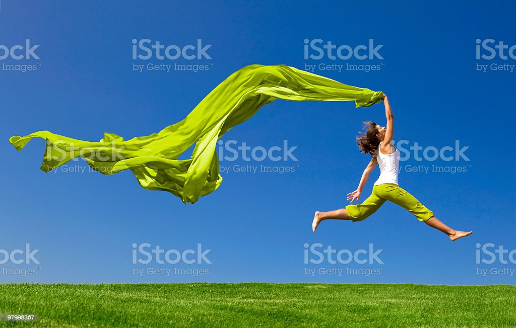 Woman jumping on green meadow with colored tissue royalty free stockfoto