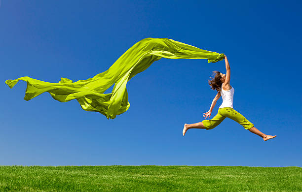 Woman jumping on green meadow with colored tissue stock photo