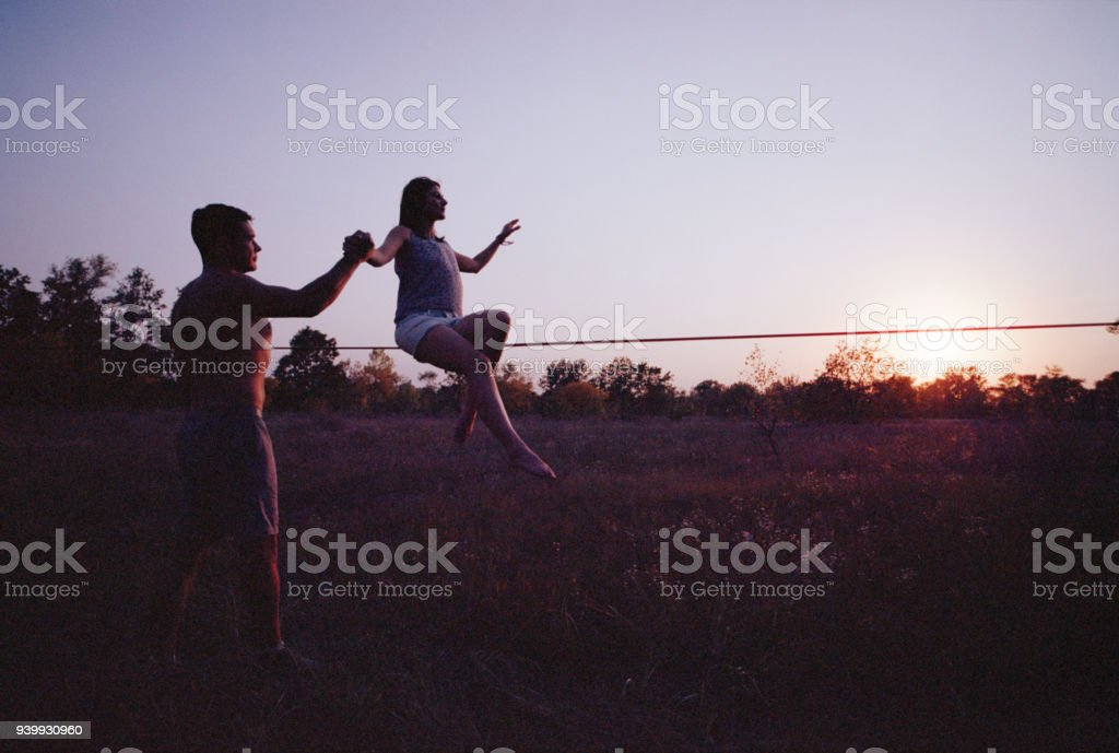 Woman jumping on slackline in the meadow at sunset. stock photo