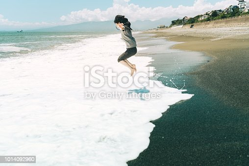 500536143istockphoto A woman jumping on the beach 1014092960