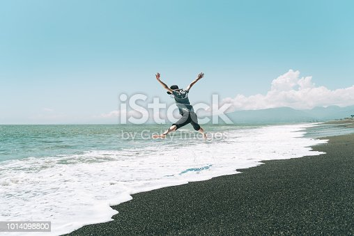 500536143istockphoto A woman jumping on the beach 1014098800