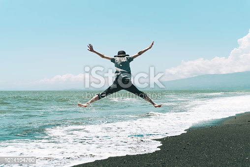 500536143istockphoto A woman jumping on the beach 1014104760