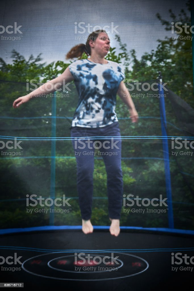 Woman jumping on trampoline stock photo