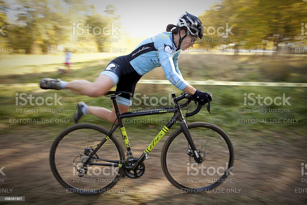 Woman jumping onto her bike during cyclocross race stock photo