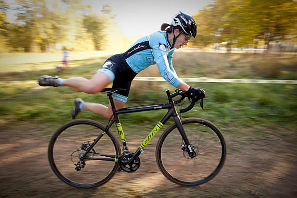 frau springen auf ihr fahrrad rennen während cyclone hudhud - cyclocross stock-fotos und bilder