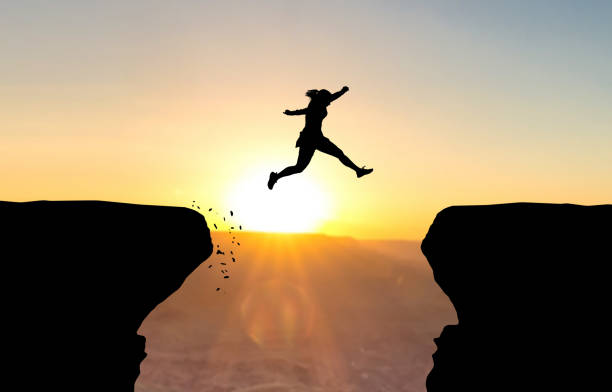 Woman jumping over abyss. Woman jumping over abyss in fornt of sunset. mid air stock pictures, royalty-free photos & images