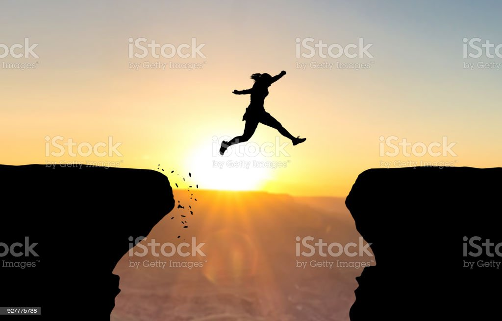 Woman jumping over abyss. - foto stock