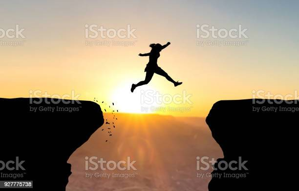 Woman jumping over abyss in fornt of sunset.