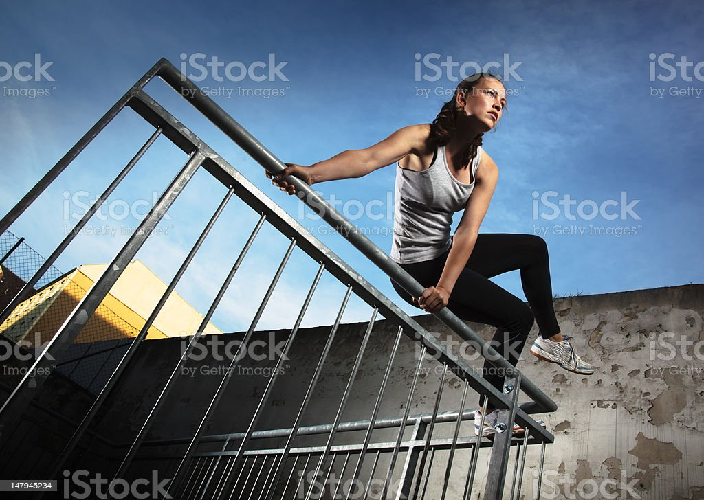 Woman jumping over fence obstacles stock photo