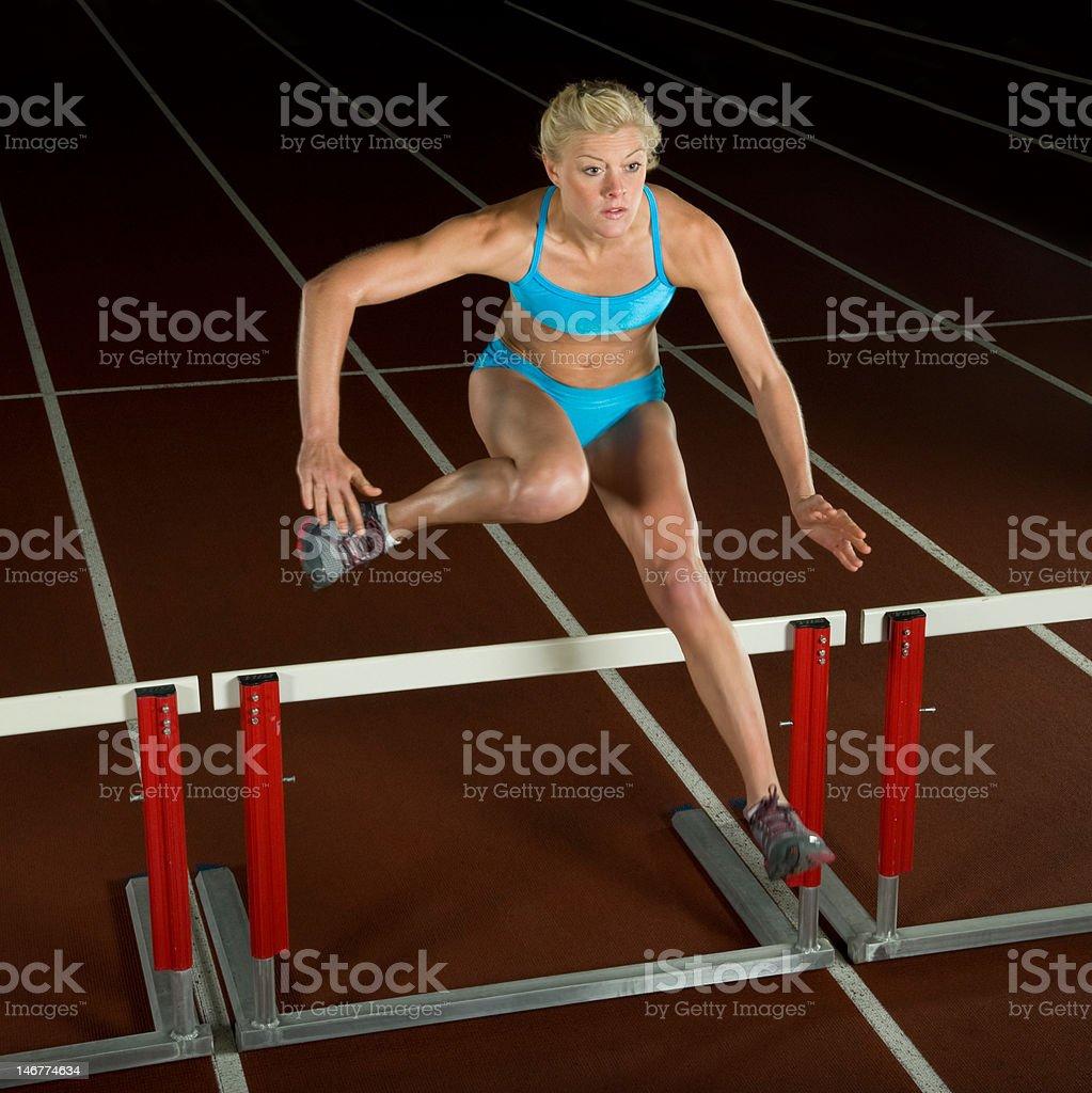 Woman Jumping Over Hurdle royalty-free stock photo