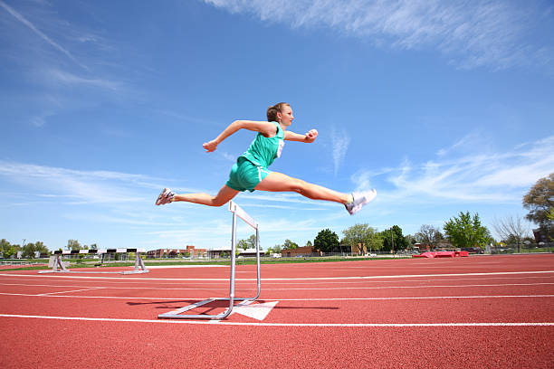 Woman jumping over hurdle Woman in mid-air jumping over hurdle women's track stock pictures, royalty-free photos & images