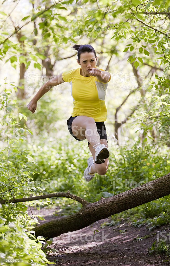 Woman Jumping Over Log royalty-free stock photo