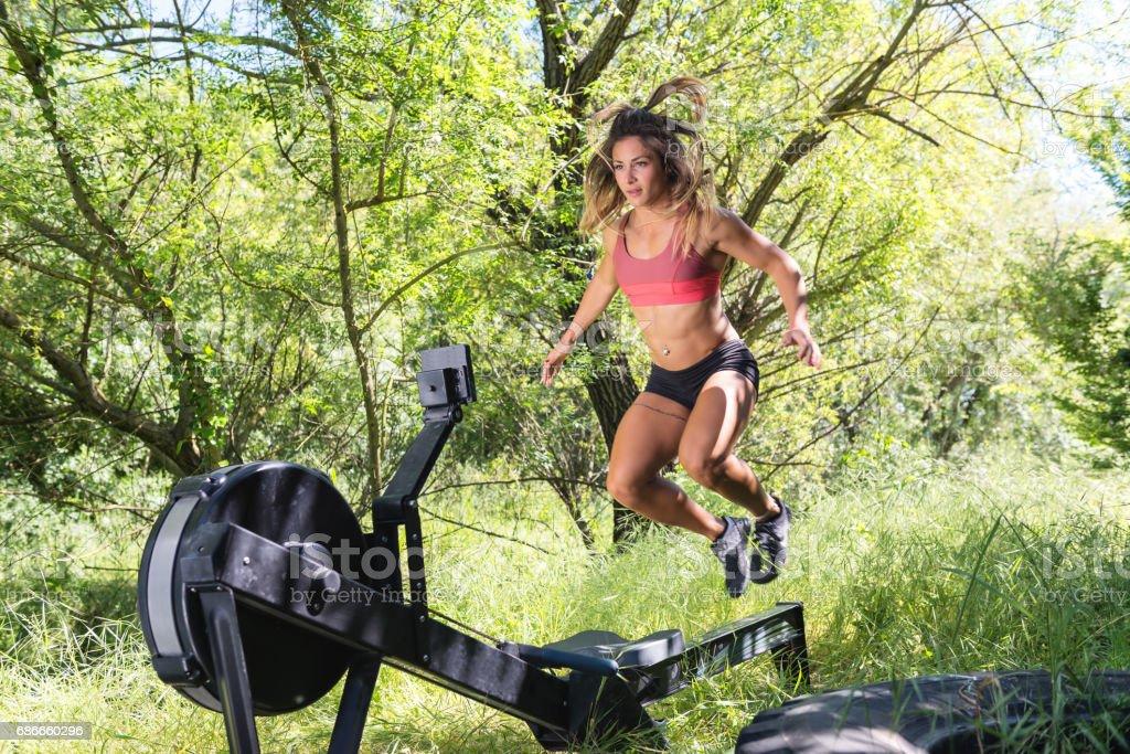 Mujer saltando por encima de la máquina de remo foto de stock libre de derechos