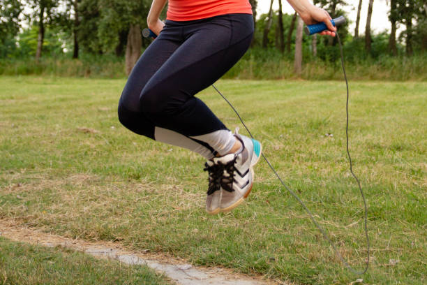 Woman jumping rope outdoors stock photo