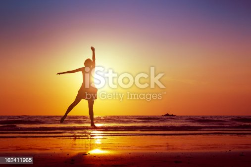 istock A woman jumping up on a beach  162411965