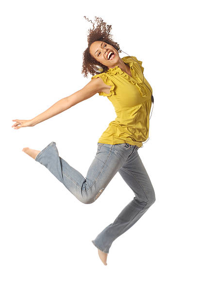 woman jumping while listening to a great song - african youth jumping for joy stock photos and pictures