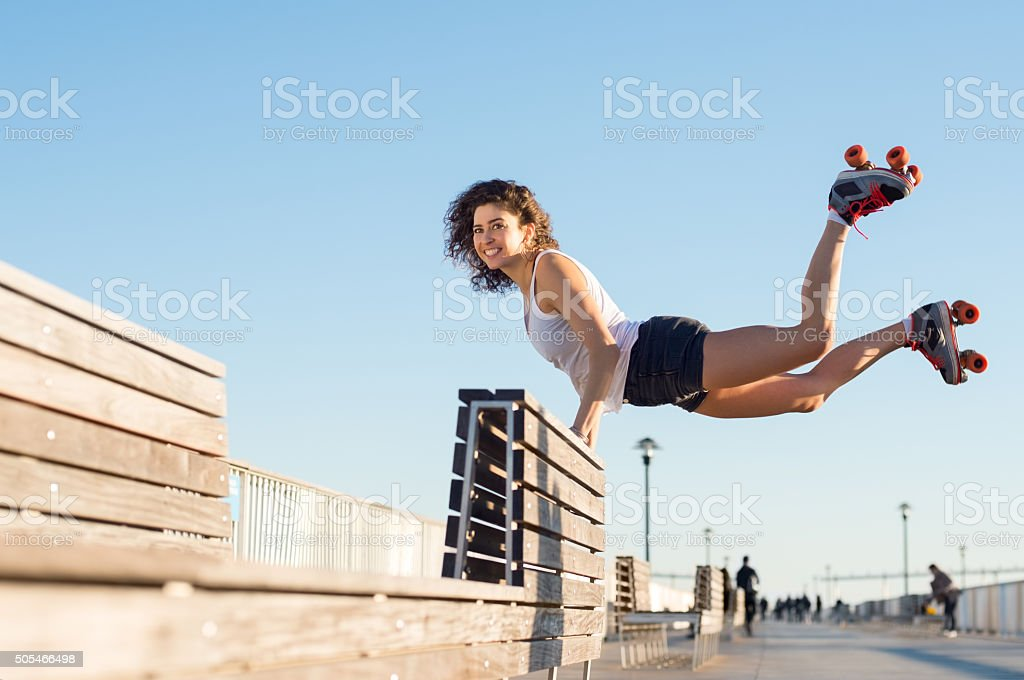 Woman jumping with roller skates stock photo