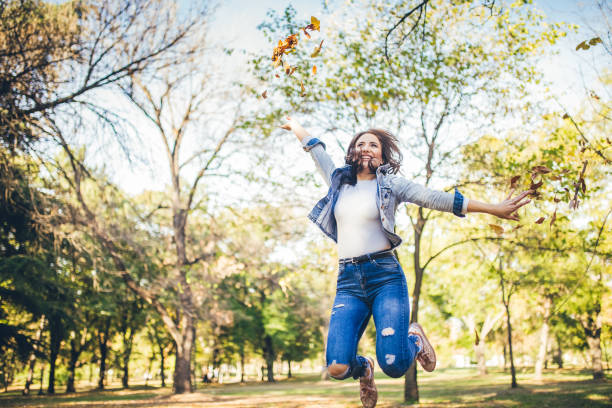 Woman jumps and throws autumn leaves stock photo