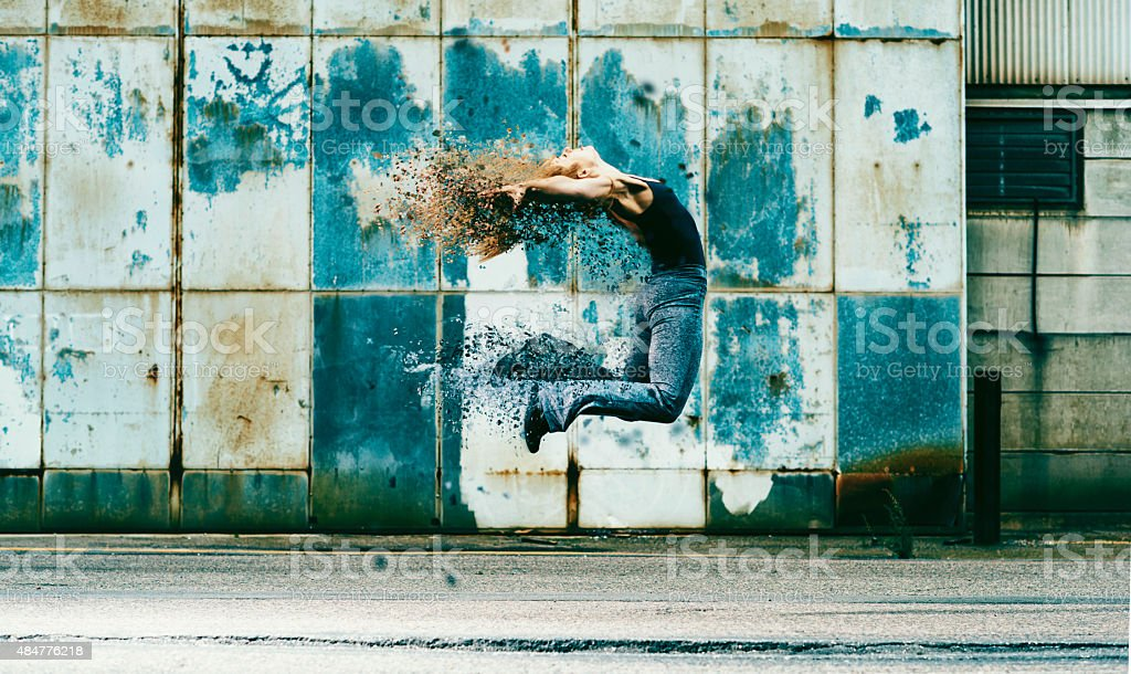 Woman jumps into the air and her body dissolves stock photo