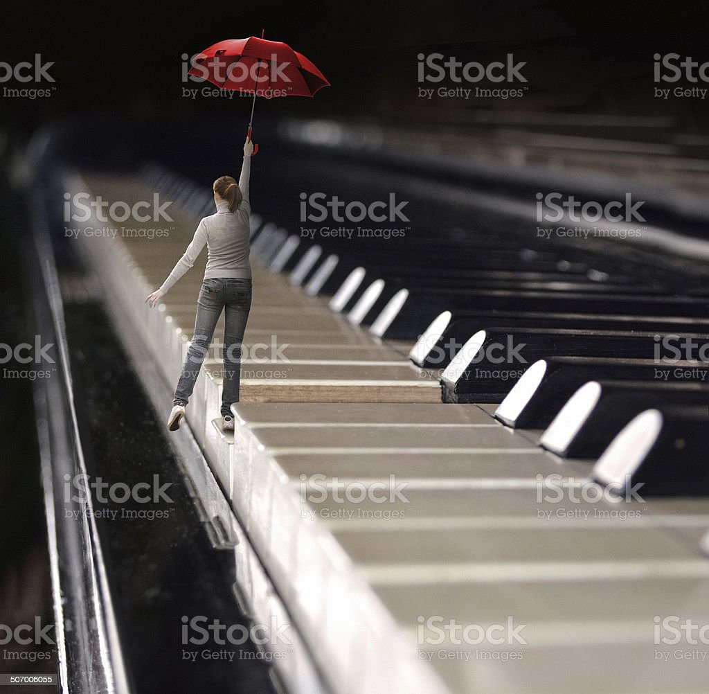 woman jumps with umbrella on a piano keyboard stock photo