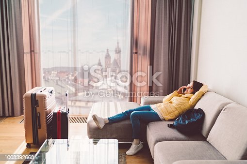 Happy woman lying down at the sofa and talking on phone