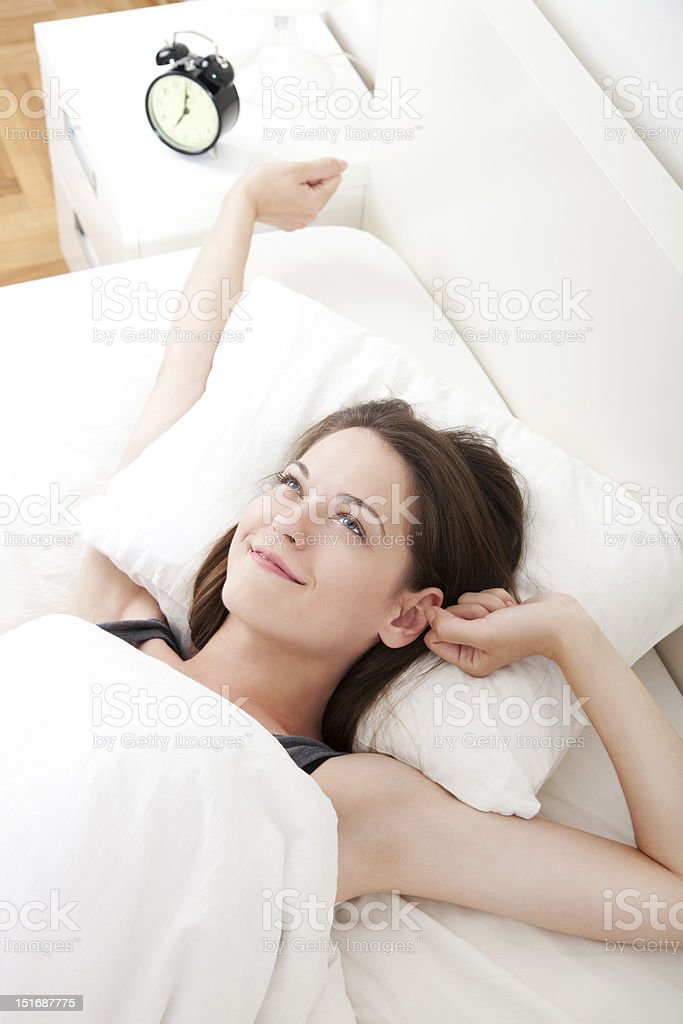 Woman just waking up and stretching stock photo