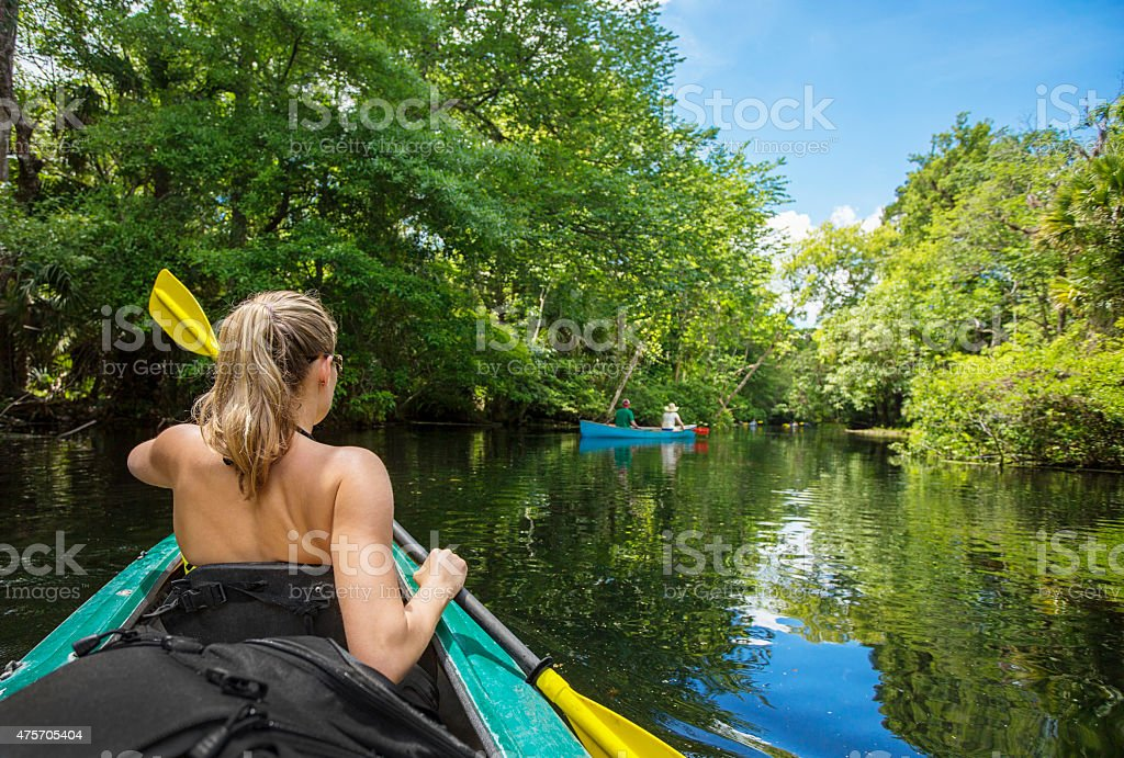 Woman Kayaking down a beautiful tropical jungle river stock photo