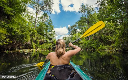 Adventuresome Woman kayaking along a beautiful tropical jungle river. Paddling along a calm beautiful river in a scenic natural backdrop