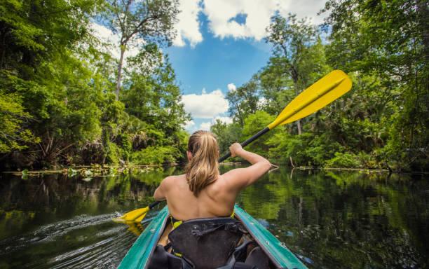 Woman Kayaking down a beautiful tropical jungle river stock photo