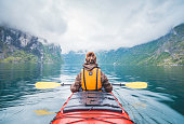 Woman kayaking in Geiranger fjord in Norway.
