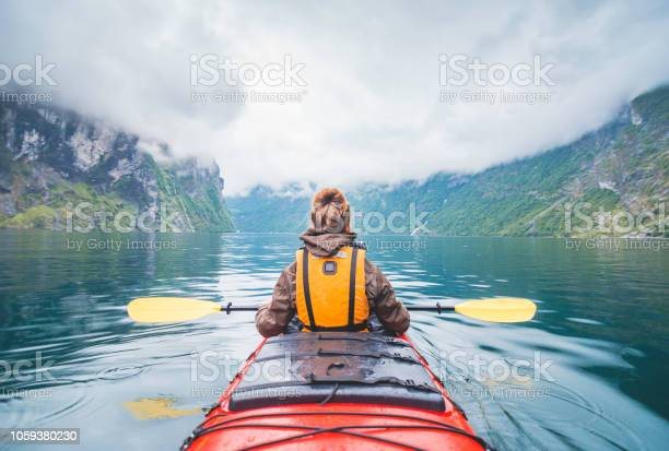 Woman kayaking in fjord in Norway.