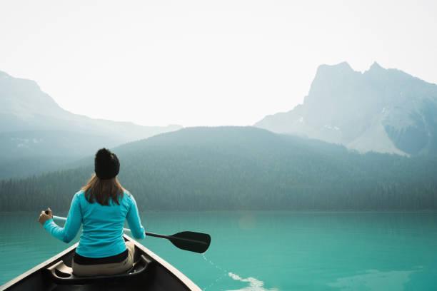 Woman kayaking in lake stock photo