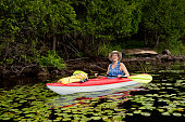 50 + woman kayaking on a lake. She is wearing hat and t-shirt over swimwear, and is enjoying her vacations. Horizontal full length outdoors shot with copy space.
