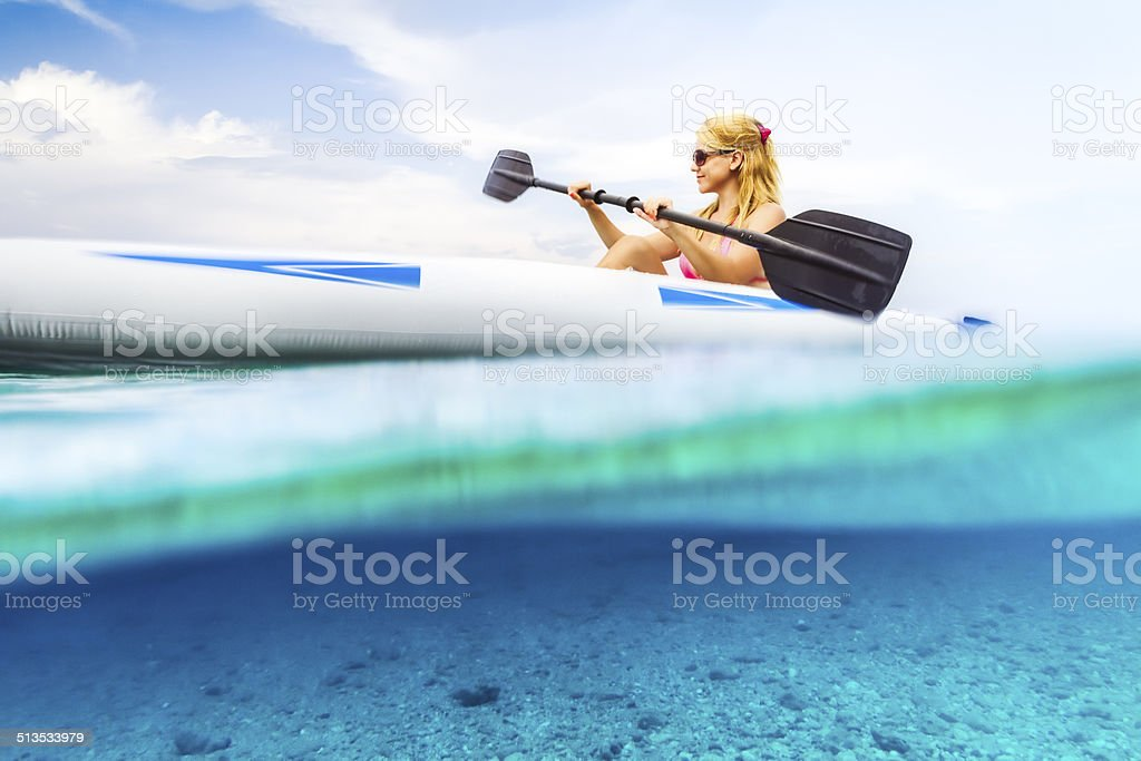 Woman kayaking on the blue sea. stock photo
