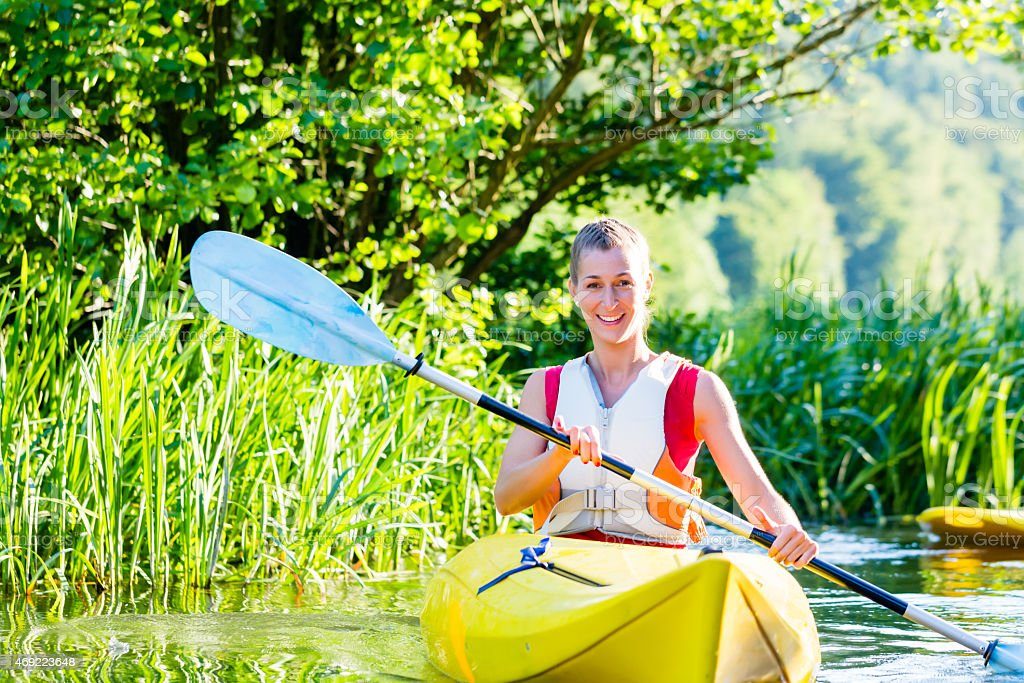 A woman kayaking on the forest river stock photo