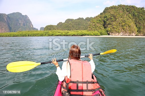 woman kayaking on the sea with sunset.Asian woman rowing on the river. Summer travel on the beach.